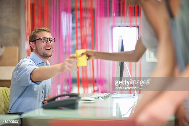 Young woman handing coffee to male colleague in office