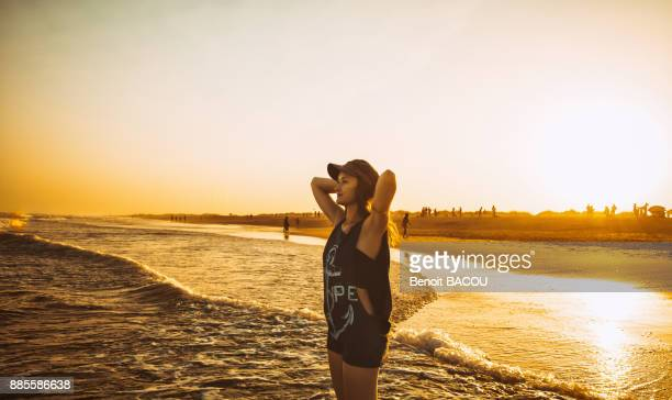 Young woman hands behind head, keep the sea on the beach Praia do Barril in a sunset, deTavira city, region of Algarve, Portugal