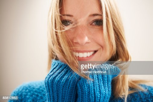Young woman, hands under chin with wind in hair : Stock Photo