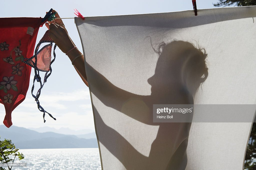 Young woman hanging clothes to dry on washing line : Stock Photo