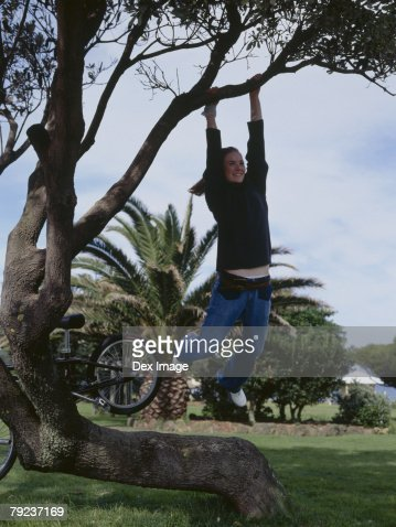 Young woman hanging from tree branch : Stock Photo