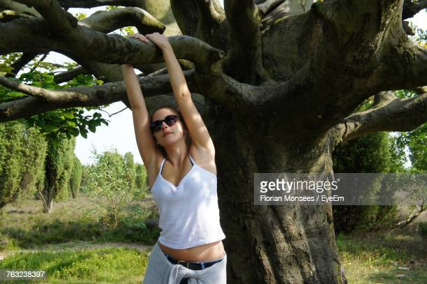 Young Woman Hanging From Tree