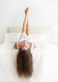 Young Woman Hanging Hair Over Edge of Bed