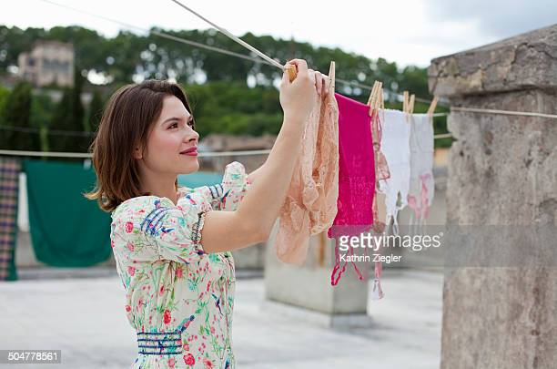 young woman hanging lingerie on clothesline