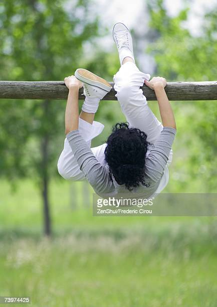 Young woman hanging on horizontal bar