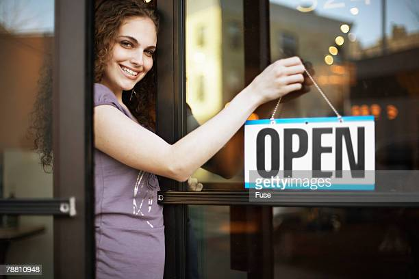 Young Woman Hanging Open Sign Outside Store
