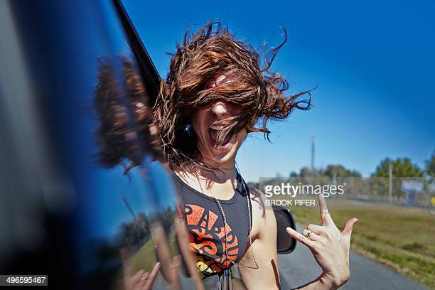 Young woman hanging out car window