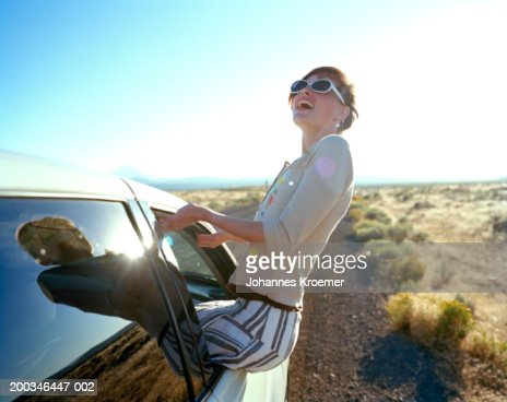 Young woman hanging out of car window, side view : Stock Photo