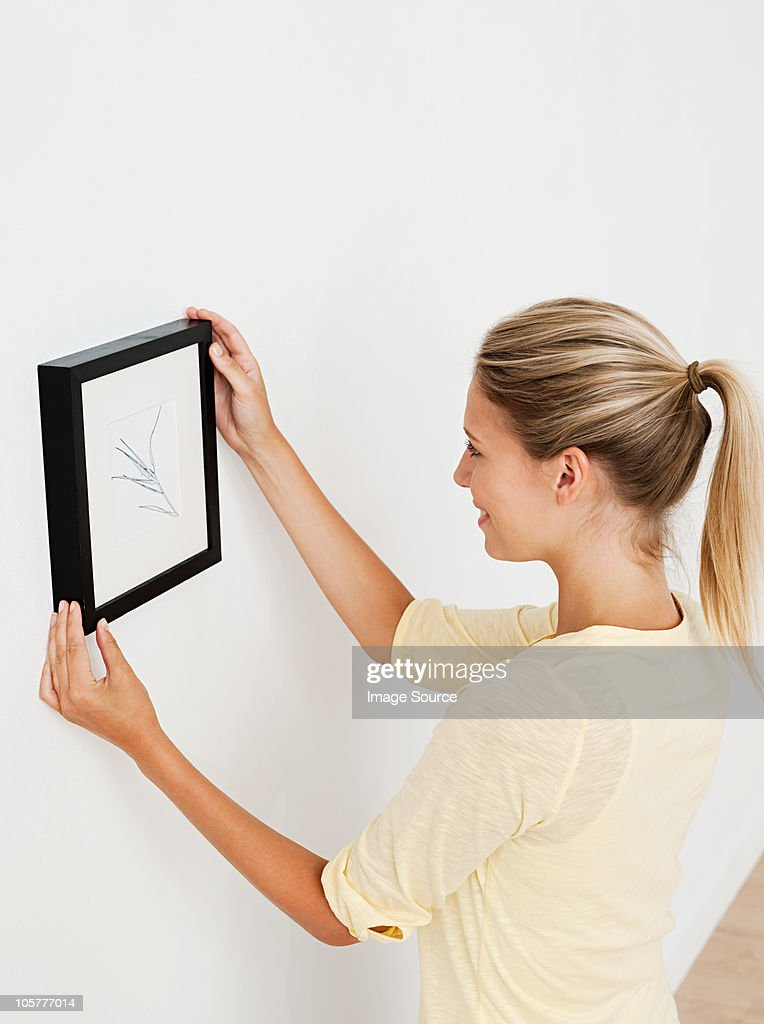 Young woman hanging picture on wall : Stock Photo