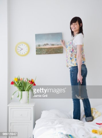 Young woman hanging up painting in bedroom : Stock-Foto