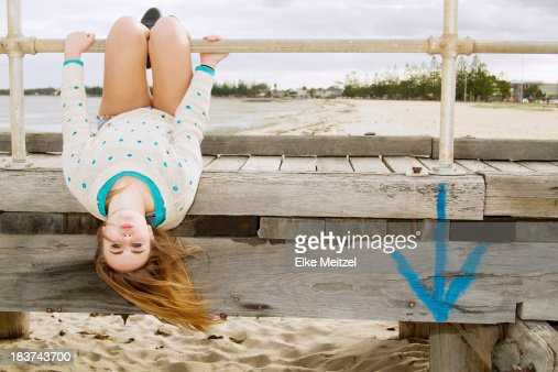Young woman hanging upside down from pier