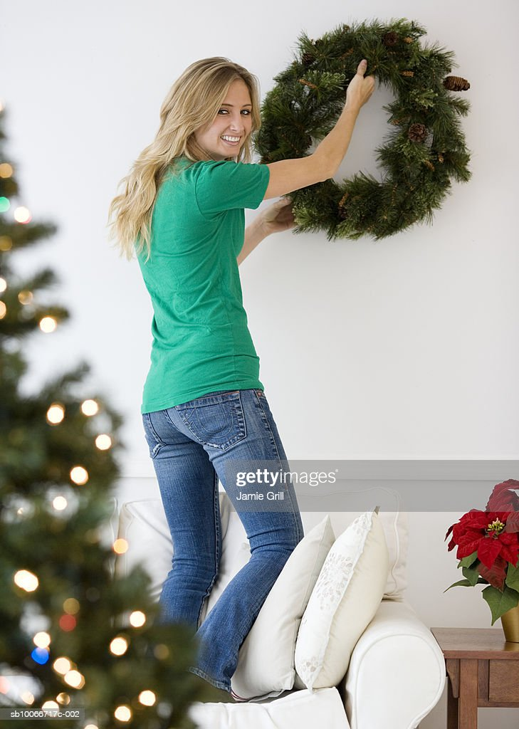 Young woman hanging wreath on wall, smiling, portrait (focus on background) : Stock Photo