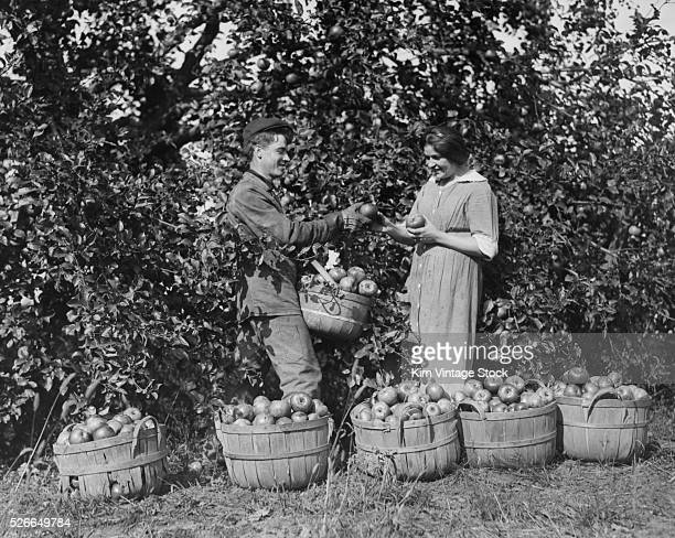 A young woman happily accepts an apple from an apple picker