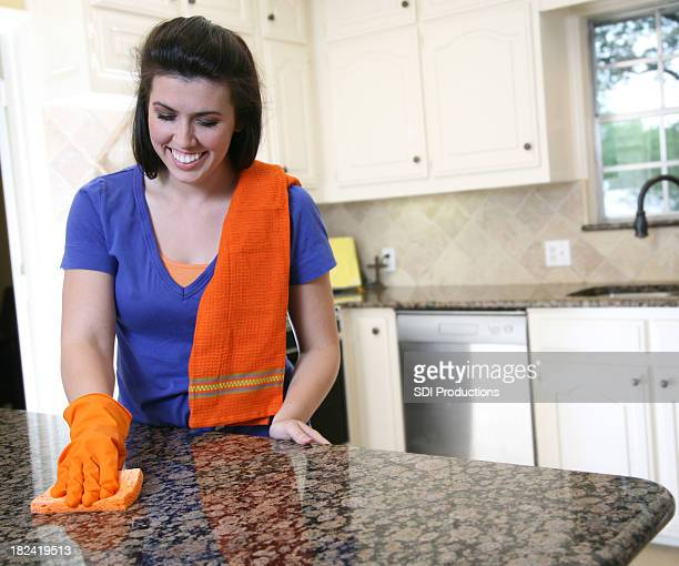 Young Woman Happily Cleaning Her Kitchen Counter With Orange Sponge