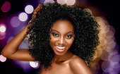 Glamourous curly hairstyle on sexy African American woman. Model has a beautiful brown skin tone. Photo taken in studio. African descent model.