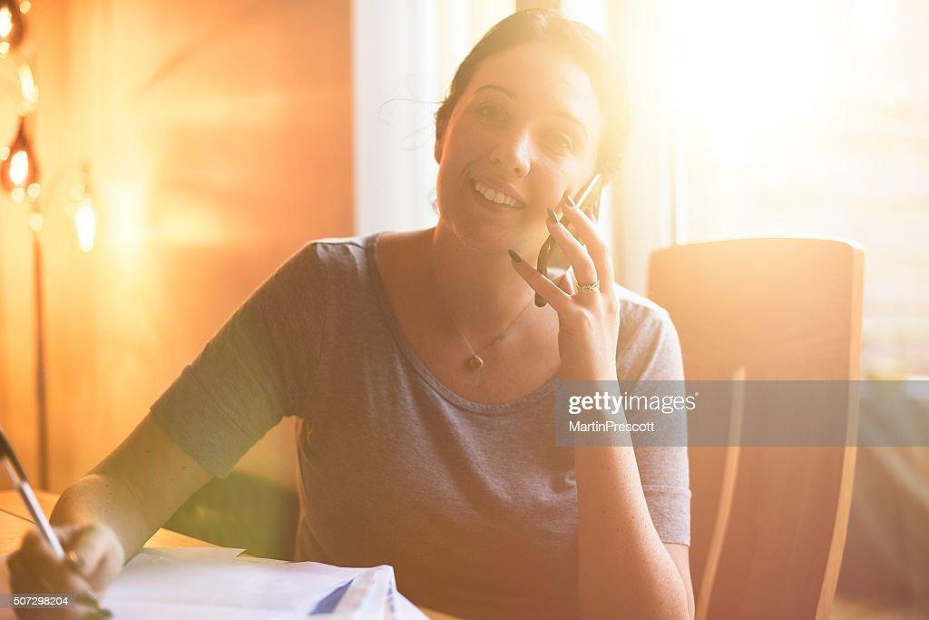 Junge Frau bietet einige gute Nachrichten am Telefon. : Stock-Foto