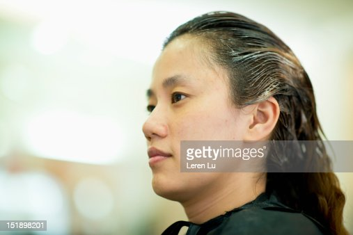 Young woman have hair colored in hair salon : Stock Photo