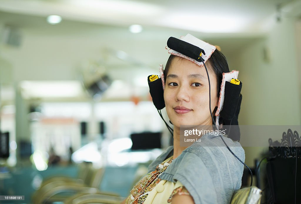 Young woman have hair permed in hair salon : Stock Photo