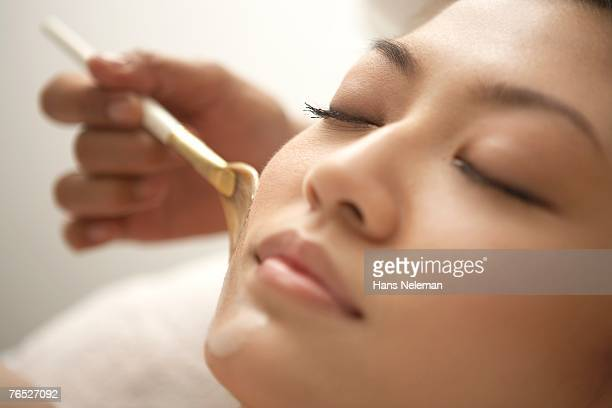 Young woman having a facial applied by brush