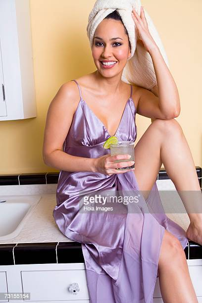 Young woman having a margarita in kitchen