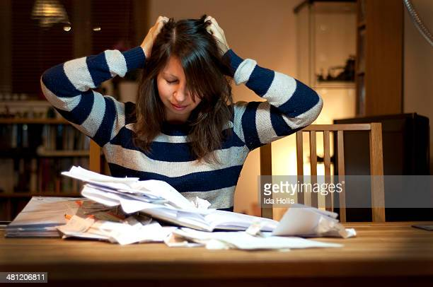 A young woman having a stressful time organising her receipts and files for a tax return