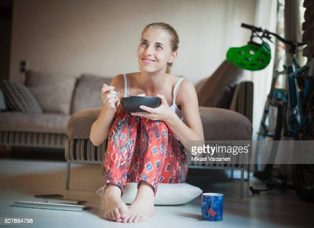 Young woman having breakfast in front of tv