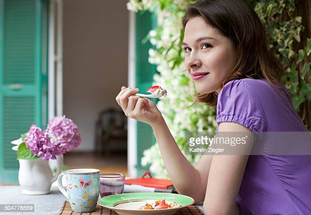 young woman having breakfast in the garden