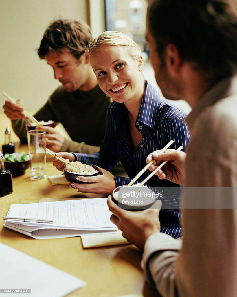 Young woman having business lunch with two men, smiling : Stock Photo