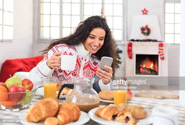 Young woman having christmas breakfast at home