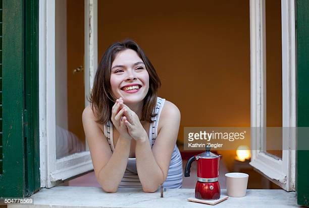 young woman having coffee at the open window