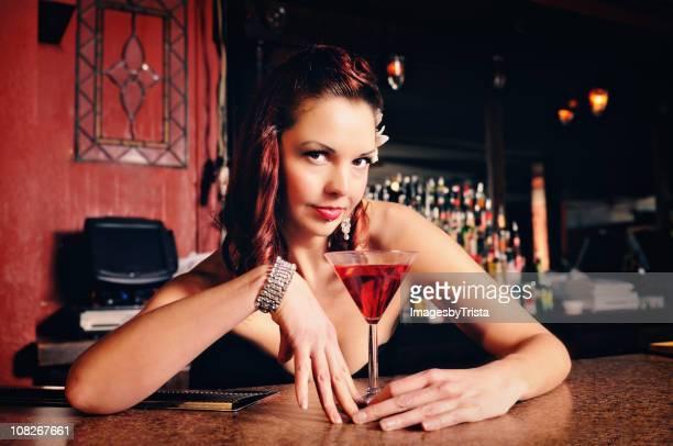 Junge Frau mit Cocktail in der Bar