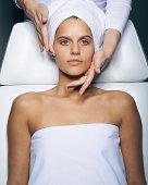 Young woman having facial treatment