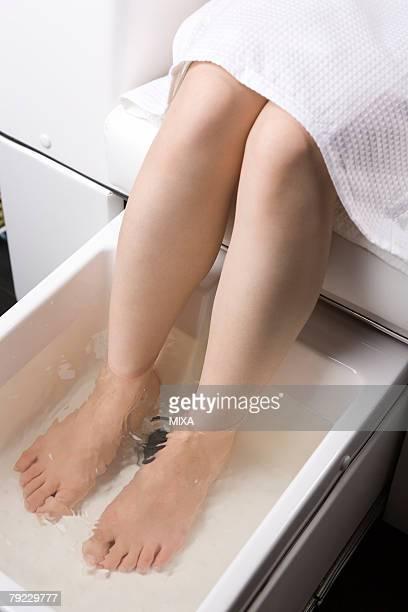 Young woman having foot bath