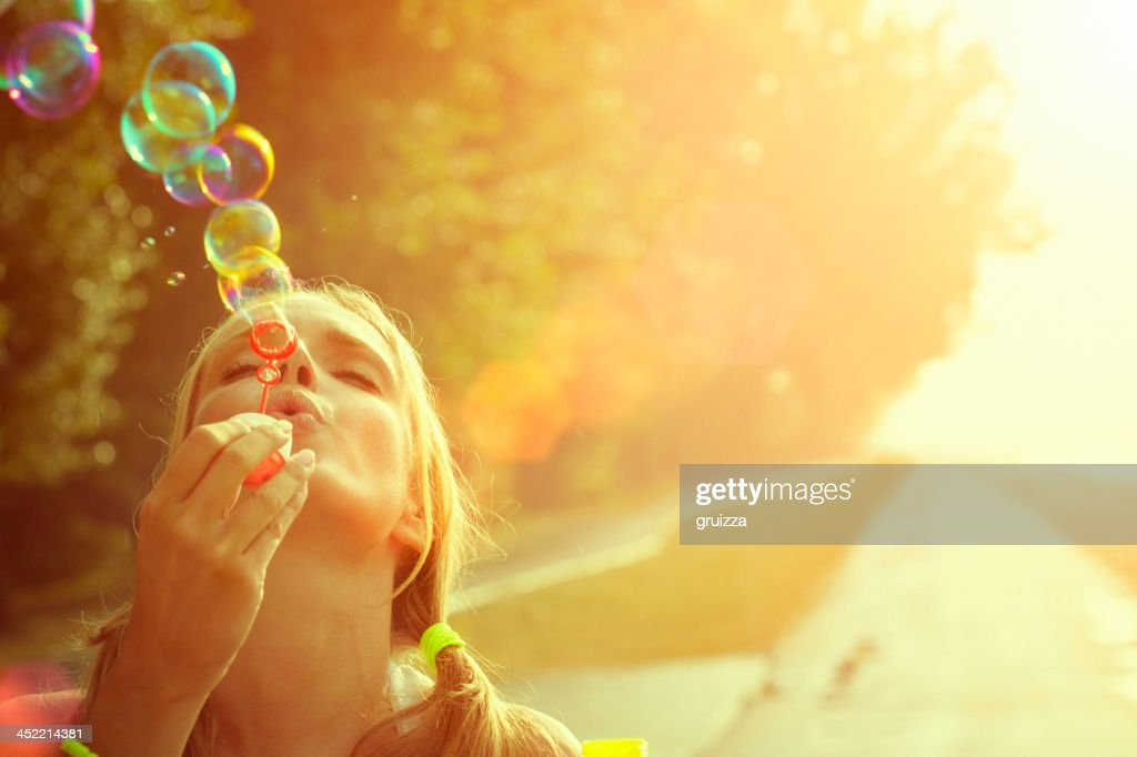 Young woman having fun and blowing bubbles outdoors
