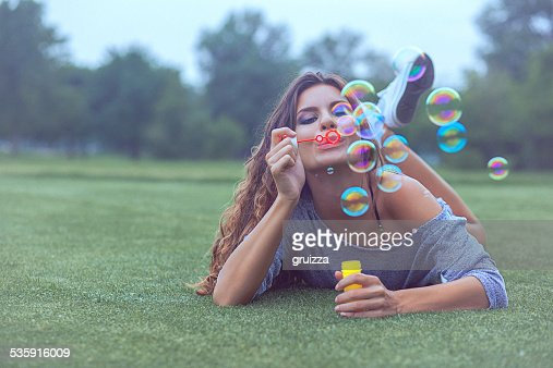 Young woman having fun and blowing bubbles outdoors : Stock Photo
