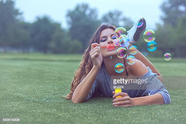 Junge Frau, die Spaß und Blasen Blasen im Freien