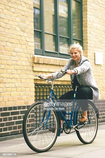 Giovane donna che si diverte guidare la sua bicicletta In città