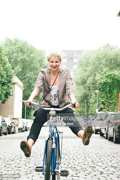 Young Woman Having Fun Riding Her Bike In City Streets