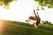 Young woman having fun swinging in sunlight