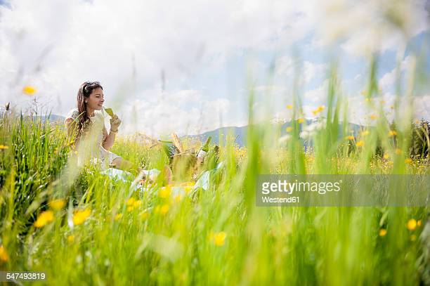Young woman having picnic on alpine meadow
