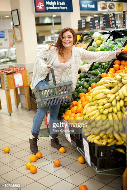 Young woman having shopping mishap with oranges