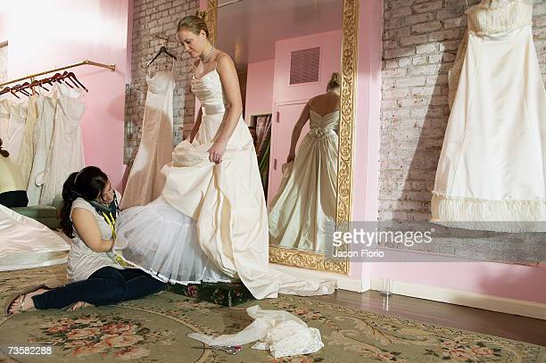 Young woman having wedding dress fitted
