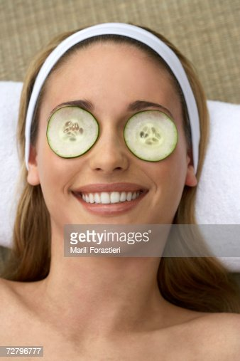 Young woman, head on pillow, with cucumber slices on eyes, close-up : Stock Photo