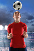 Young woman heading soccer ball inside large stadium