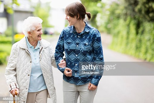 young caregiver helping senior woman walking in the street