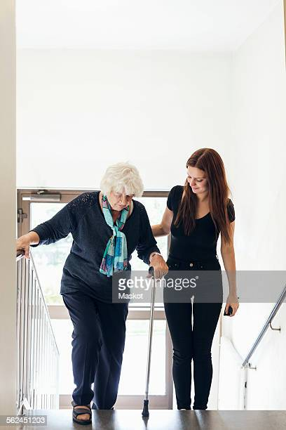 Young woman helping grandmother to climb steps