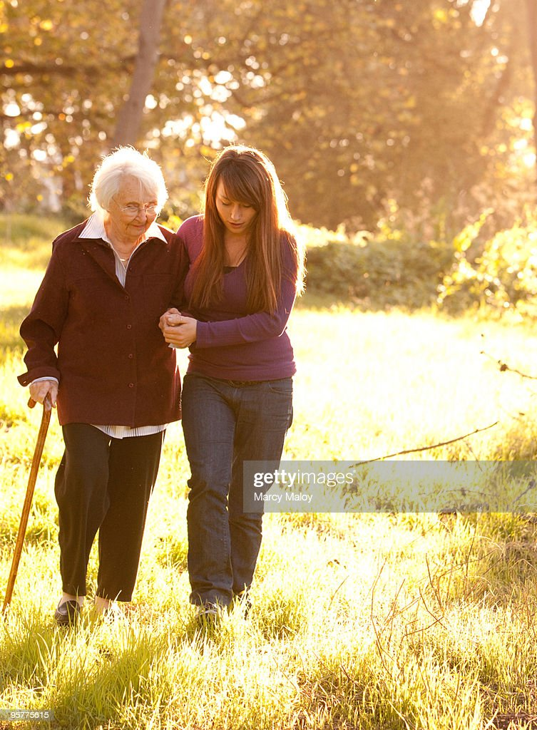 Young Woman helping Older Women walk in woods : Stock Photo