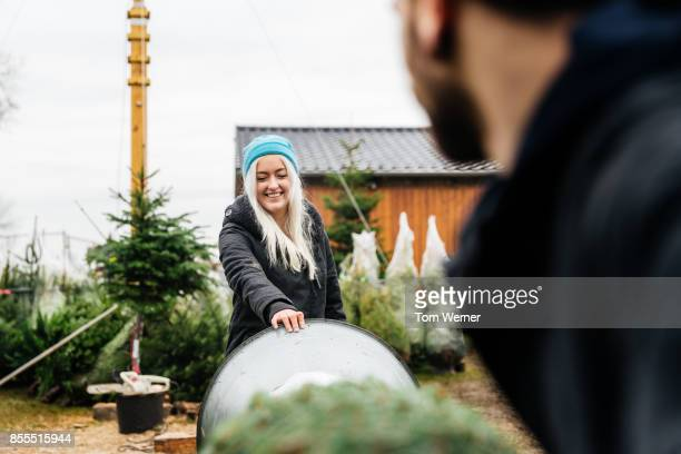 Young Woman Helping Partner To Wrap Freshly Cut Down Pine Tree