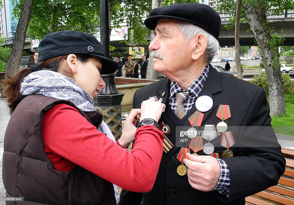 A young woman helps a World War II veteran to adjust the orange and black St. George ribbon, commemorating Soviet Union's triumph in WWII, during Victory Day celebration in Baku, the capital of Azerbaijan, on May 9, 2013. Azerbaijan as well as the other former Soviet republics celebrates the 1945 victory over Nazi Germany on May 9, the date of the Nazis' capitulation to the Soviet Union, which took place in the evening on May 8, 1945 (May 9 by Moscow Time), following the original capitulation Germany agreed earlier to the joint Allied forces on the Western Front.