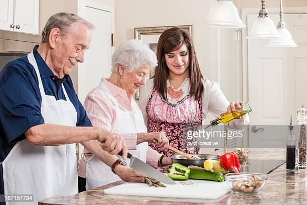 Junge Frau helfen ältere paar Kochen